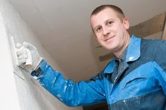 Plasterer at work. Plasterer at indoor renovation decoration with putty knife Royalty Free Stock Image