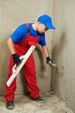 Plasterer at work. Plasterer at indoor wall renovation decoration with float and trowel Royalty Free Stock Photography