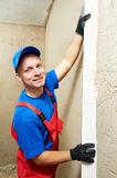 Plasterer at work. Plasterer at indoor wall renovation decoration with sleeker Royalty Free Stock Image