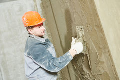Plasterer at work with wall Royalty Free Stock Image