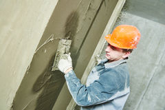 Plasterer at work with wall. Construction worker plasterer with trowel plastering a wall Stock Image