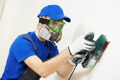 Plasterer worker with sander at wall filling. Home improvement plasterer worker in protective mask and glasses working with sander for smoothing wall surface Stock Images