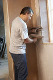 Plasterer Working On Interior Wall Stock Image