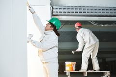Plasterers at indoor wall work Stock Photos