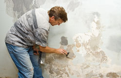 Plastering. Plasterer at work doing indoor house repair with plaster Stock Images