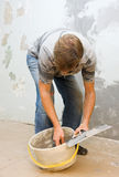 Plastering. Plasterer at work doing indoor house repair with plaster Stock Photo