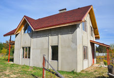 Plastering Exterior House Wall Ready for Painting.  Roofing Construction with  Asphalt Shingles Installation Exterior. Royalty Free Stock Image