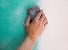 Plastering man hand sanding the plaste in drywall seam Royalty Free Stock Image