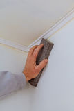 Plastering man hand sanding the plaste in drywall seam plasterboard. Sanding the wall Royalty Free Stock Photography