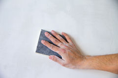Plastering man hand sanding the plaster Royalty Free Stock Images