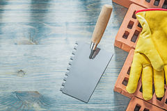 Plastering trowel red bricks safety gloves on wood board brickla Royalty Free Stock Photo