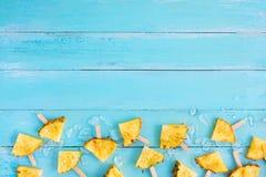 Plasterka popsicle ananasowi kije z lodem na drewnianej deski błękitnym kolorze obraz royalty free