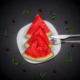 Plasterki świeżego juta czerwony arbuz na białym talerzu słuzyć z rozwidleniem i nożem Obraz Royalty Free