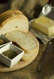 Plasterki świeży chleb z masłem, pikantność i ziele na drewnianej desce, zdjęcia royalty free