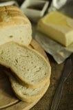 Plasterki świeży chleb z masłem, pikantność i ziele na drewnianej desce, obrazy royalty free