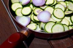 Plasterki czerwona cebula i zucchini obrazy royalty free