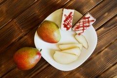 Plasterki czerwone bonkrety i domowej roboty torty są w białym talerzu na drewnianym stole robić sosnowe deski Bufet w autentyczn zdjęcie royalty free