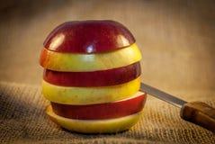 Plasterki czerwoni i żółci jabłka z nożem fotografia stock