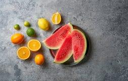 Plasterki czerwony arbuz i świezi cytrusy na nieociosanym tle Pomarańcze i wapno Odgórny widok obrazy royalty free