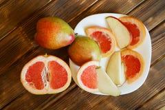 Plasterki czerwony grapefruitowy i bonkrety kłamają w białym talerzu na drewnianym stole robić sosnowe deski Bufet w autentycznym fotografia stock