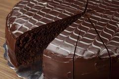 Plasterki duży czekoladowy tort na drewnianym stole fotografia royalty free