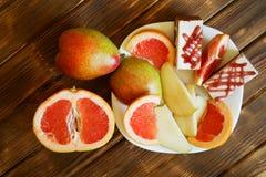 Plasterki grapefruitowy, bonkrety i torty, s? w bia?ym talerzu na drewnianym stole robi? sosnowe deski Bufet w autentyczny natura fotografia royalty free