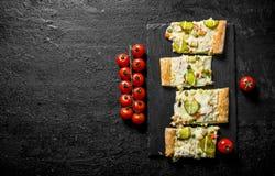 Plasterki jarzynowa pizza na ciapanie desce z pomidorami na gałąź zdjęcia royalty free