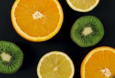 Plasterki kiwi, cytryna i pomarańcze na czarnym tle na kredowej desce, Tam jest miejsce dla teksta zdjęcia stock