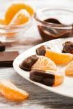 Plasterki mandarynki zakończenie w ciekłej czekoladzie słuzyć na białym talerzu Selekcyjna ostrość fotografia stock