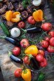 Plasterki mięso na grillu na drewnianym stole z warzywami, Lato pinkin w naturze z wyśmienicie jedzeniem obraz royalty free