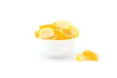 Plasterki owocowa cukierek pomarańcze, cytryna w filiżance odizolowywającej i Obrazy Royalty Free