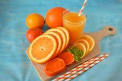Plasterki pomarańcze, mandarynka, cytryna i koloru żółtego sok w szkle, fotografia royalty free