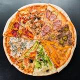 Plasterki różne pizze zbierali w jeden pizzy na zmroku z powrotem obraz stock