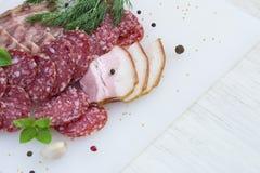 Plasterki salami i bekon na białym tle, odgórny widok Zdjęcie Royalty Free