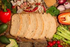 Plasterki sourdough chleb spadają kaskadą w centrum rama Różnorodni kolorowi i świezi warzywa układają wokoło obrazy stock