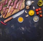 Plasterki surowa wołowina z ziele i czosnkiem na tnącej desce z pomidorami na gałąź, rabatowy miejsce dla teksta na błękitnym dre Zdjęcie Stock