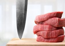 Plasterki surowy mięso z ostrym nożem Obraz Stock