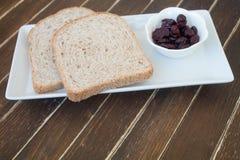 Plasterki wysuszony chleb i czarne jagody na drewnie Fotografia Stock