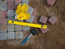 Plasterung Stein blockiert Gummihammerniveauhandschuhe und Band measu Lizenzfreies Stockbild