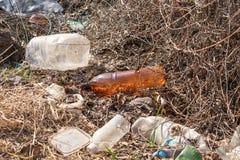 Plastic afval in de droge struiken stock foto