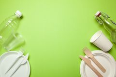 Plastic And Eco-friendly Disposable Utensils Made Of Bamboo Wood And Paper On A Green. Fork, Knives, Plates, Cups And Bottle Royalty Free Stock Photo
