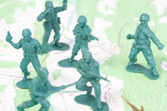 Plastic Army Men Fighting on Topographic Map. Royalty Free Stock Photos