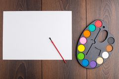 Plastic art palette and canvas. On wooden background Royalty Free Stock Images