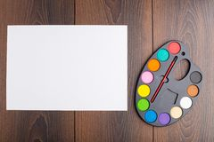 Plastic art palette and canvas. On wooden background Royalty Free Stock Photography