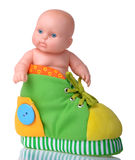 Plastic Baby Doll sitting in the colored boot Royalty Free Stock Photography
