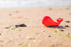Plastic toy red whale on the seashore for background Royalty Free Stock Photography