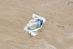 Plastic Bag on the Beach. Single use plastic shopping bag washed up on a beach and part buried in the sand an example of the many pieces of garbage in the oceans stock photo