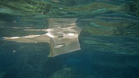 Plastic bag floats on water surface, pollution concept with copy space royalty free stock photos