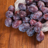 Plastic bag with plums on wood Royalty Free Stock Photography