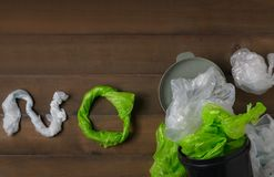 Plastic bags in bin on wood background royalty free stock image